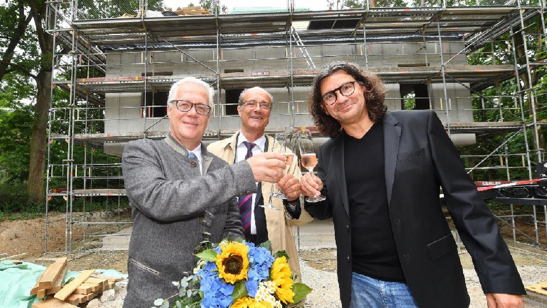 Kanzler Christian Zens, Prof. Günther Leugering und Architekt Tim Gräßl (v. l.) stoßen beim Richtfest des neuen Gästehauses der Universität gut gelaunt an.