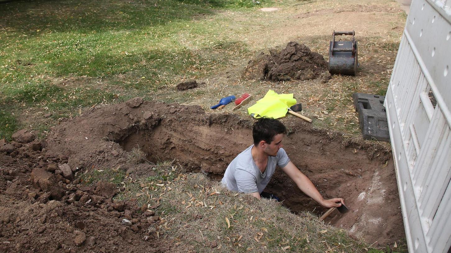 Eine der Schürfgrabungen ist in der Grünanlage am Schlossgraben. Praktikant Martin Butz kratzt mit der Garten-Hacke Erde ab, die nach Artefakten abgesucht wird.