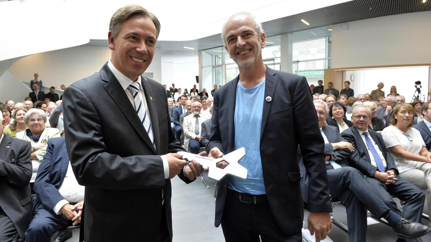 Architekt Andreas Marth (re.)  überreichte Landrat Alexander Tritthart den Schlüssel fürs neue Haus in der Form des Gebäudes