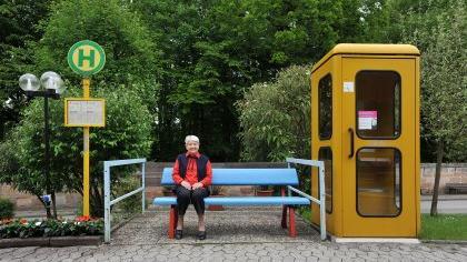 Die Täuschung vor dem Heimeingang ist nahezu perfekt: ein Halteschild, ein Fahrplan, dazu eine Bank und eine gelbe Telefonzelle, die der Telekom ausgemustert und kostenlos zur Verfügung gestellt wurde.