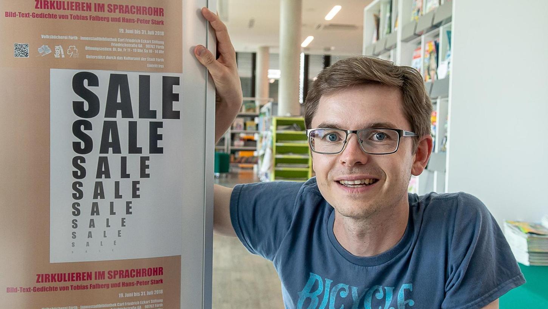 """""""Kunst ist nichts Abgehobenes"""": Tobias Falberg neben dem Ausstellungsplakat, das eine der in Fürth noch bis Mitte August zu sehenden Arbeiten präsentiert."""