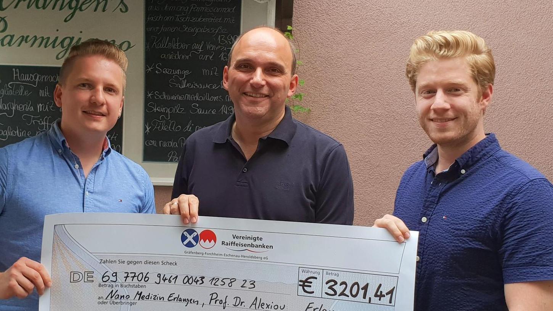 Markus Urban (rechts) und Markus Hack (links) bei der Übergabe der Spende an Professor Christoph Alexiou.