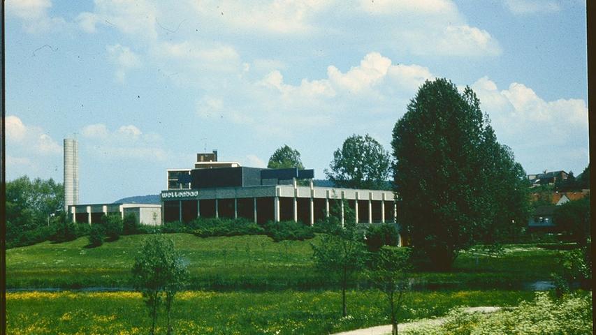 Das Treuchtlinger Hallenwellenbad in den 1970er Jahren, noch ohne den 1979 bis 1981 ergänzten Thermalbereich. Davor die begradigte Altmühl.