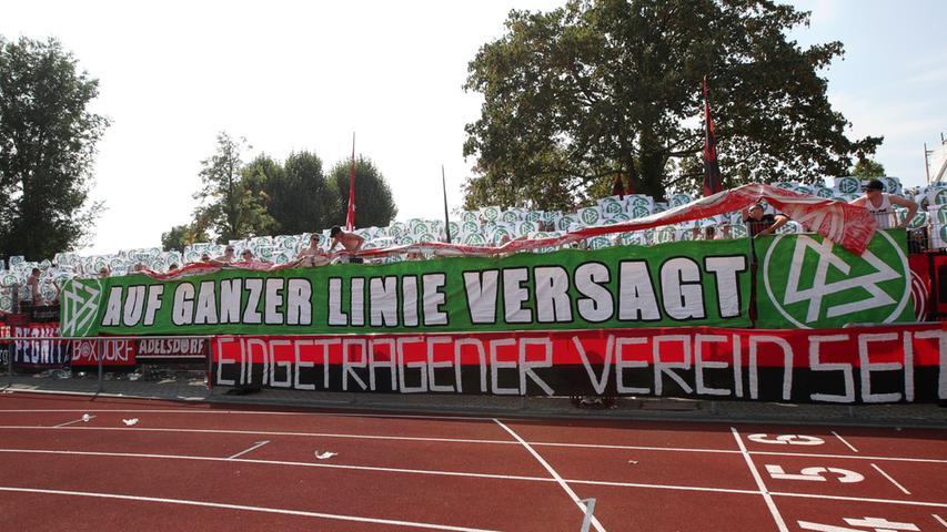 Nach einer kurzen Abkühlung packen die Fans des 1. FC Nürnberg ein Banner mit einer Botschaft in Richtung DFB aus.