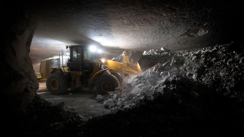 Mächtige Radlader, die fast zu der Decke in vier Metern Höhe reichen, schaffen den am Vorabend gesprengten Anhydrit aus der Grube.