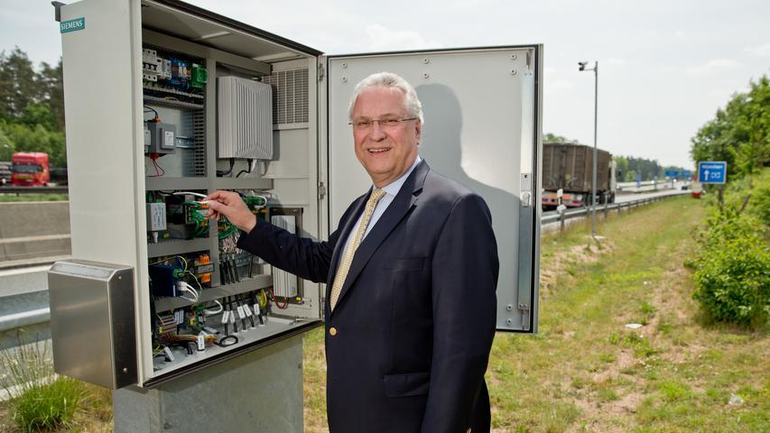 Der bayerische Innenminister Joachim Herrmann (CSU), steht am 2015 in Nürnberg auf einem Rastplatz entlang der Autobahn Nürnberg-München (A9) an einem Schaltschrank ein neues elektronischen Leitsystem für Lkw vor...