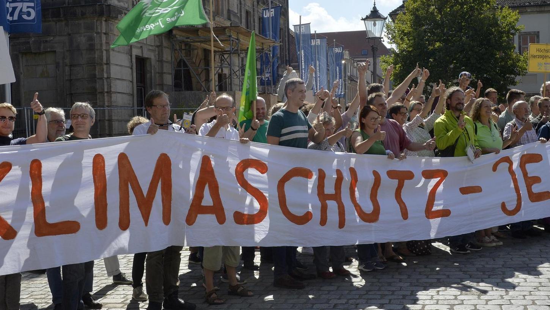 """""""Rise for Climate"""": Unter diesem Motto machten sich auf dem Erlanger Schlossplatz rund 200 Menschen für mehr Klimaschutz stark."""