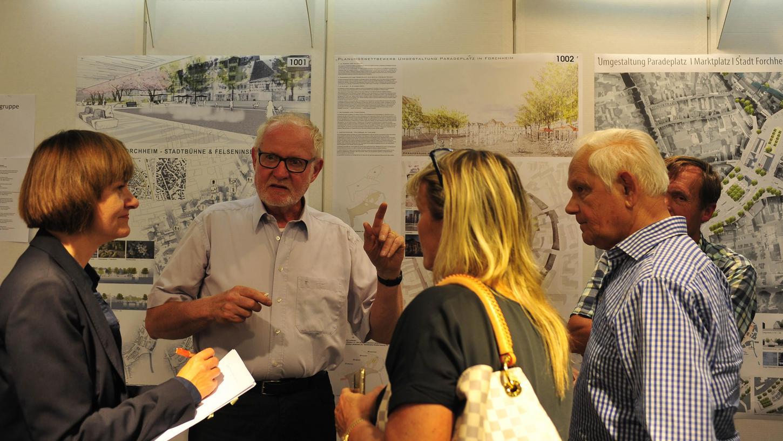 Jury-Präsident Professor Gerd Aufmkolk erklärt bei der Auftaktveranstaltung Bürgern, was die einzelnen Entwürfe zur Umgestaltung des Paradeplatzes auszeichnet.