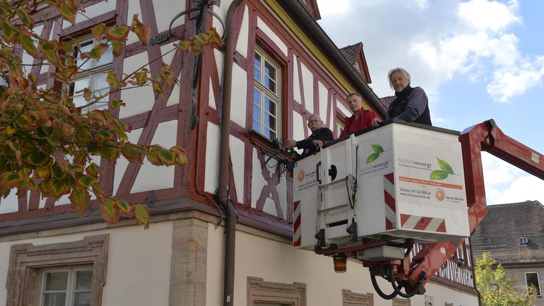 Bei der Arbeit: Markus Stirn (Mi.) und Klaus Metzler (r.) montieren gerade Strahler an die Fassade des Alten Rathauses. Dazu werden sie von Jürgen Gügel (l.) mit dem Hubsteiger in die richtige Höhe gehievt.