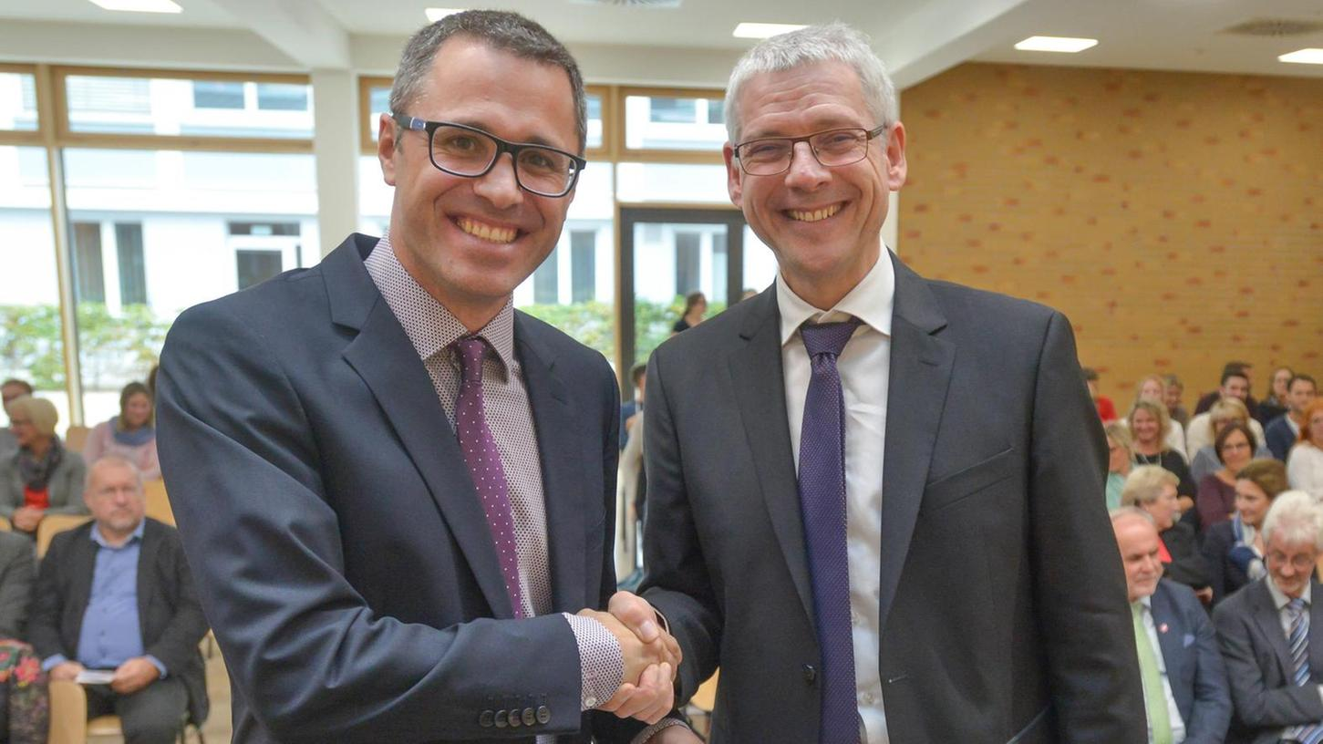 Der Ministerialbeauftragte für Realschulen in Mittelfranken, Michael Schmidt (r.) übergibt die Ernennungsurkunde an den neuen Schulleiter Stefan Bindner.
