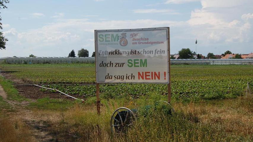 """Vor allem seitens der Landwirte gibt es Gegenwind bei der Städtebaulichen Entwicklungsmaßnahme Marienberg: """"Entwicklung ist schon fein, doch zur SEM da sag ich NEIN!"""" steht auf diesem Protestplakat am Rand von Marienberg- und Flughafenstraße geschrieben."""