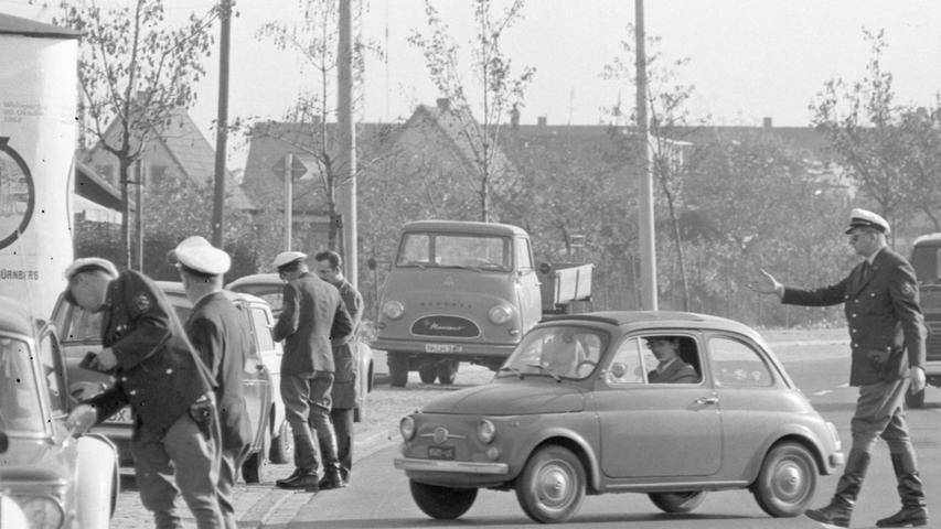 Auch 1968 gab es schon Polizeikontrollen in Nürnberg. Während ein kleiner Fiat 500 gerade auf den Seitenstreifen gelenkt wird, steht im Bildhintergrund völlig unbehelligt ein heute höchst seltener Kleinlastwagen vom Typ Hanomag Markant herum. Mehr historische Straßenszenen aus Nürnberg können Sie sich hier anschauen.