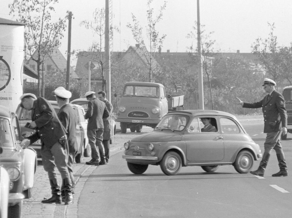 Dieses Bild täuscht: der Polizeibeamte fällt vor dem Kraftfahrer nicht auf die Knie. Bei einem kleinen Auto und einem großen Polizisten ist ein Gespräch durch das Wagenfenster in gebückter Haltung nicht zu vermeiden.