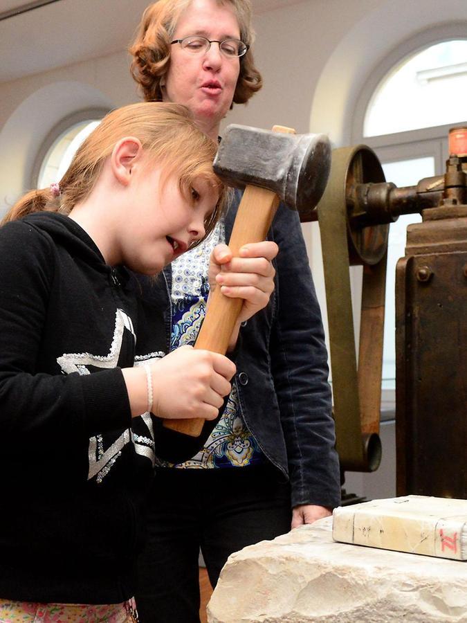 Dass es anstrengend ist, will man feinstes Blattgold herstellen, merkt das Mädchen, das beherzt zum schweren Hammer greift.