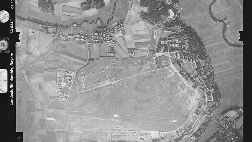 Nachdem der Flughafen in Fürth-Atzenhof 1915 als Fliegerschule für die Königlich Bayrischen Flieger gebaut wurde, fungierte er später als Zivil-Flughafen, zunächst unter dem Titel Fürth-Nürnberg, später wurde er in Nürnberg-Fürth umbenannt. Auf diesem Bild aus dem Jahr 1963 hatte schon lange die US Army die Kontrolle über das Gelände. Der berühmte Schuttberg, der heutige Solarberg, am Nordende des Flughafens existierte zu diesem Zeitpunkt noch nicht. Vom Main-Donau-Kanal ist nichts zu sehen, im Osten schlängelt sich die Regnitz entlang, im Norden die Zenn.