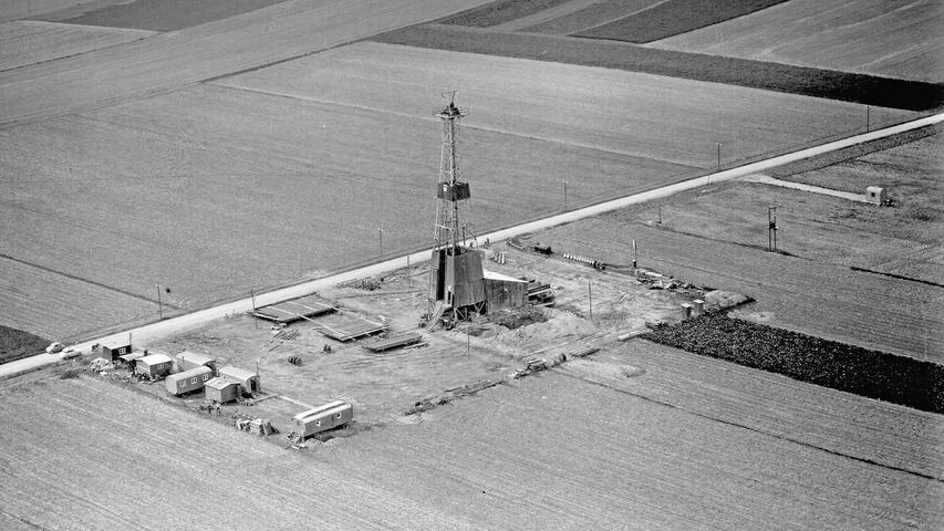 Doch nicht nur am Tegernsee wurde nach Erdöl gebohrt. Vor allem in den 1950ern und 1960ern boomte die Förderung an etlichen Stellen im südbayerischen Molassebecken. Auf dem Bild ist ein Bohrturm in Ampfing zu sehen, wo seit 1954 Erdöl aus 1900 Metern Tiefe geholt wurde.