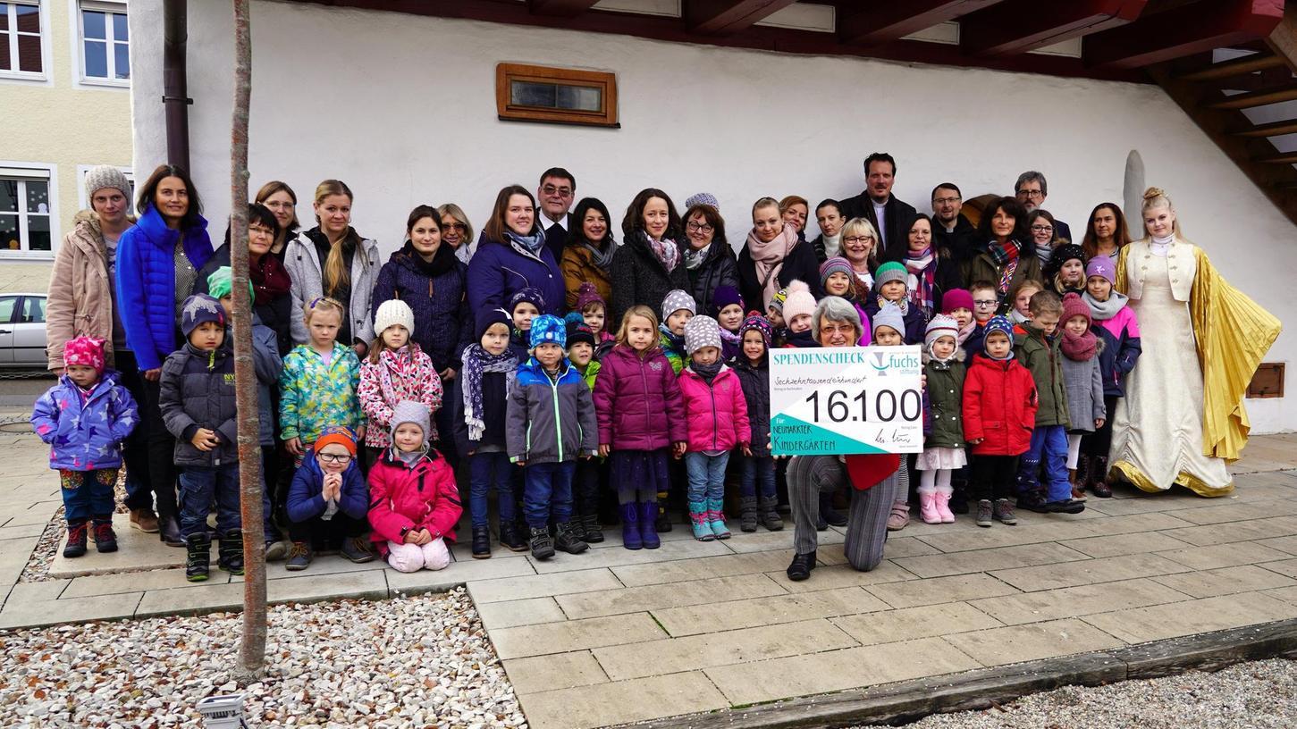 Waltraud Fuchs (mit dem Scheck) hat eine große adventliche Freude parat für die Kinder, die einen der 20 Kindergärten in Neumarkt besuchen: 16 100 Euro hat die Fuchs-Stiftung gespendet. Auch das Christkind kam dazu.