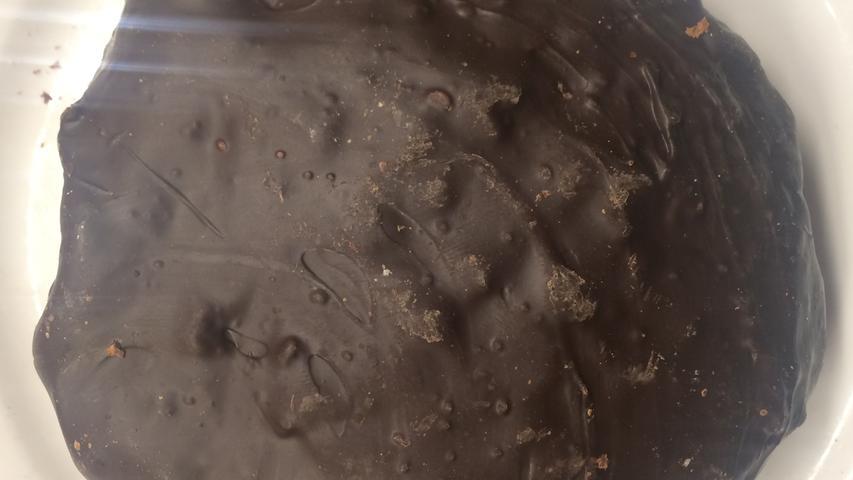 In Nürnberg oft als 'der' Geheimtipp gehandelt, mit einigen Filialen in der Stadt verteilt. Kommt extrem muskulös daher, übergossen mit Unmengen an Bitterkuvertüre und rustikaler Optik, die handwerkliche Herstellung geradezu impliziert. In der Nase dann auch Extreme: Viel Orangeat und Zitronat mit fruchtig-herben Zitrusschalenaromen, schöne Mischung aus kandierter Süße und Frucht. Viele Gewürze, vor allem viel Zimt. Am Gaumen geht's heftig weiter: Deutlich knackende Schokolade bleibt allzeit präsent, Nüsse wirken vor allem durch grobe Struktur, geschmacklich bleiben sie unauffällig...