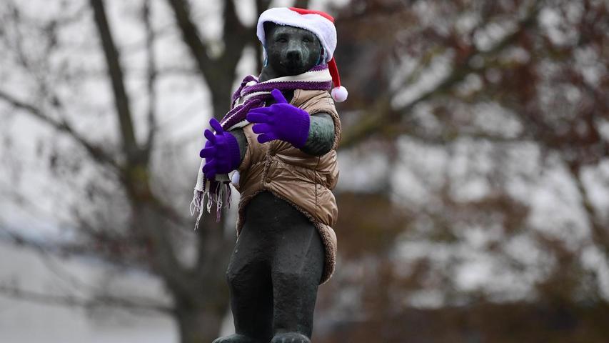 Da steht er auf seinem Sockel und trotzt seit vielen Jahren Wind und Wetter: Passend zum einsetzenden Winterwetter präsentiert sich der Bär warm verpackt.