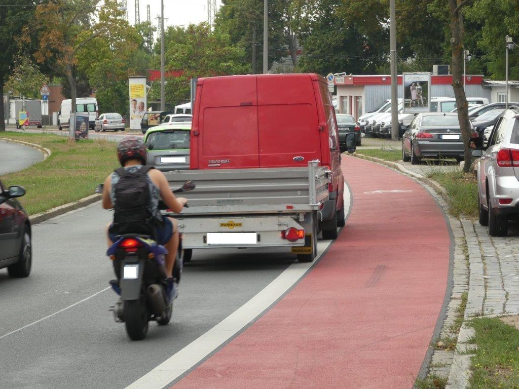 """Wenn Fahrzeuge auf einer """"überbreiten"""" Spur wie hier in der Minervastraße nebeneinander fahren, obwohl der Platz hierfür nicht ausreicht, dann kommen sie den Radfahrern gefährlich nah. Die vorgeschriebenen 1,50m Überholabstand werden so nicht eingehalten."""