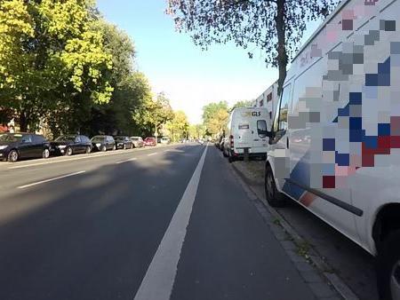 """Parkende Kfz neben Radstreifen wie hier in der Marienbergstraße stellen immer eine Gefahr für Radfahrer dar: durch sich plötzlich öffnende Autotüren (sog. """"Dooring"""") kann es zu schlimmen Unfällen kommen. Radfahrer müssen deshalb 1 m Abstand einhalten. Doch dann fährt man bereits auf der weißen Markierung des Radstreifens und kommt den von hinten überholenden Kfz gefährlich nahe."""