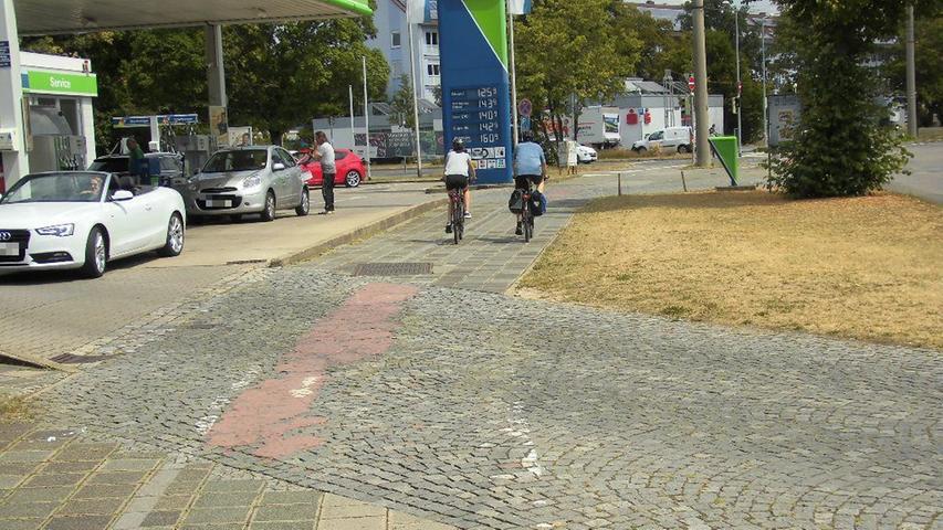 """...die Roteinfärbung der Radwegefurt ist schon längst verblasst, Fahrradpiktogramme nicht mehr erkennbar und auch das Verkehrszeichen """"Radweg kreuzt"""" bei der Ausfahrt fehlt. Deshalb kommt es immer wieder zu brenzligen Situationen."""