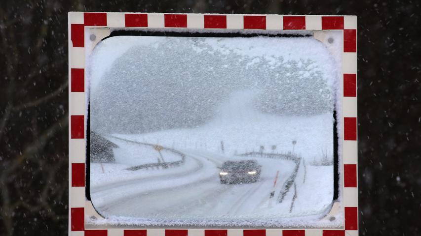 Die Schneemassen haben auch das Ostallgäu erreicht: Ein Auto fährt über  eine eingeschneite Straße im Luftkurort Nesselwang am Rande der Allgäuer Alpen.