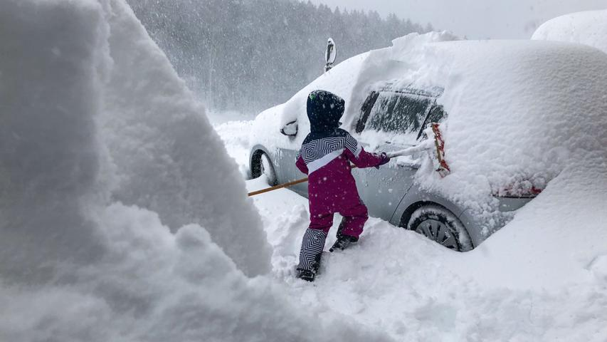 Besonders viel Schnee gibt es derzeit in Österreich: Bevor sich Autofahrer im Salzburger Land auf die verschneiten Straßen wagen können, müssen sie ihre Fahrzeuge erst von den Schneemassen befreien. In Henndorf kehrt ein Kind mit einem Besen Schnee von einem PKW.