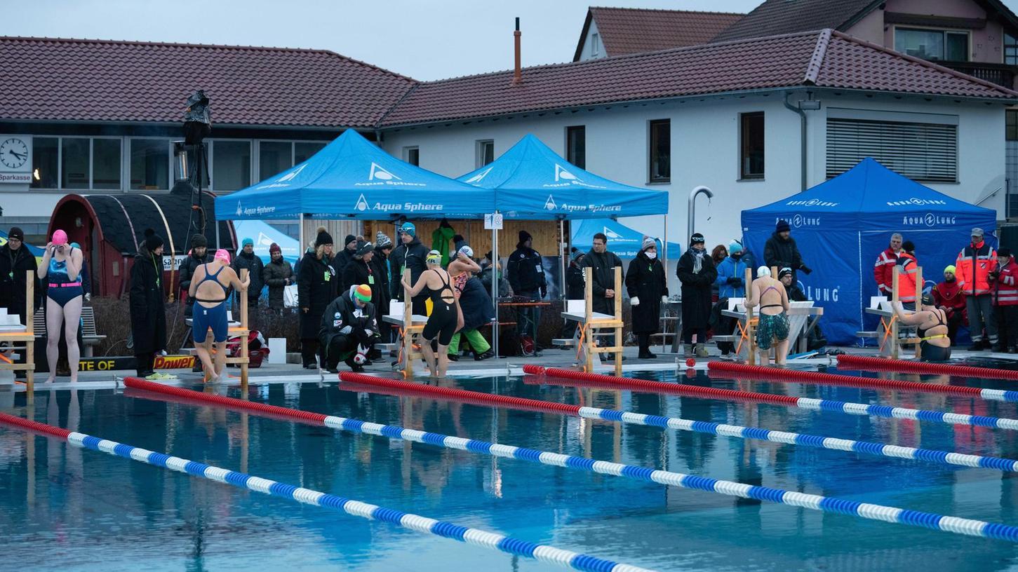 Während Betreuer, Kampfrichter und Publikum draußen dick vermummt der Kälte trotzen, steigen die Schwimmerinnen im Badeanzug ins eiskalte Wasser.