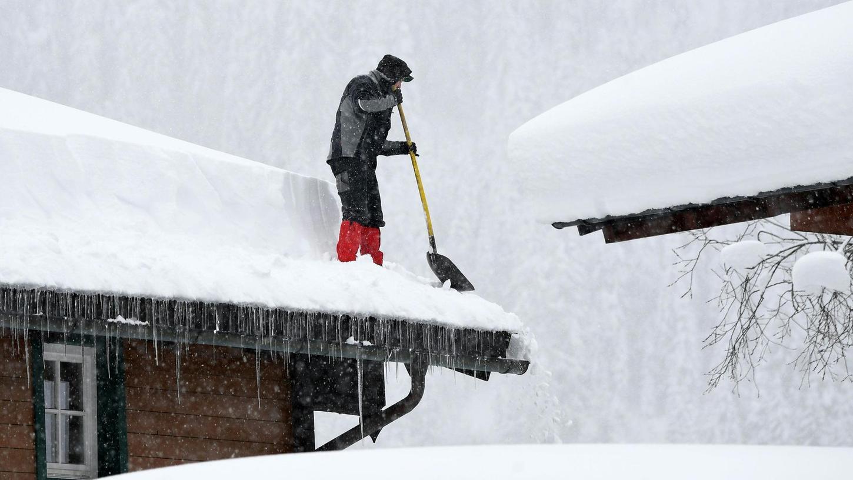 Ein Helfer befreit in Österreich ein Dach von der Schneelast. Auch im südlichen Bayern ist die Wetterlage weiter angespannt. Kräfte aus ganz Bayern machten sich gestern auf den Weg ins Katastrophengebiet. 15 Mitglieder der THW Neumarkt sind in Reit im Winkl im Einsatz.
