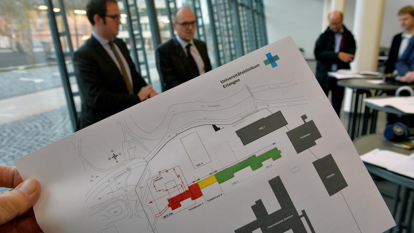 Im Zuge der Ausweitung des TRC und dem Bau eines Max-Planck-Zentrums soll der Bau zum größten Teil abgerissen werden. Der Plan im Vordergrund zeigt des Kopfgebäudes mit Bauphasen, dahinter OB Florian Janik und Heinrich Iro, Ärztlicher Direktor der Univerersitätskliniken.