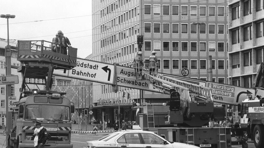 Ups, schon war es passiert: Ein Reparaturtrupp musste in den 1990er-Jahren an den Plärrer ausrücken, weil ein Lastwagen eine Schilderbrücke gerammt hatte. Links im Bild: Ein damals fast schon historischer Turmwagen mit ausfahrbarer Arbeitsbühne. Es handelt sich um einen Mercedes-Benz LP, die Baureihe stammt aus den 1960er- und 1970er-Jahren. Die Nürnberger Polizei fuhr damals die dritte Baureihe des 3er-BMWs, die sich heute gerade aus dem täglichen Straßenbild verabschiedet.