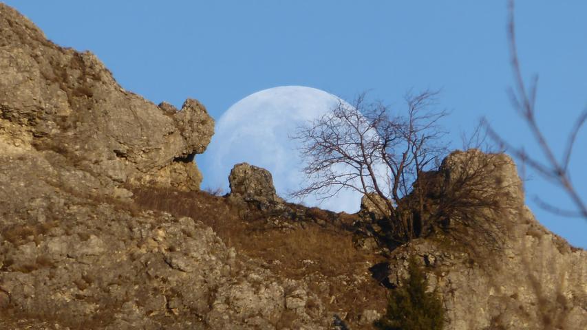 Riesig wirkt der Mond, wie er hier über die Felsen des Walberla spitzt.