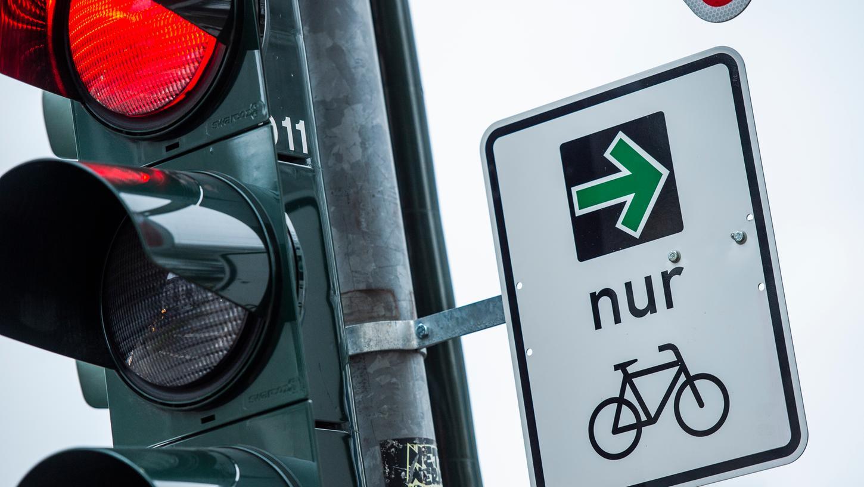 An einer Ampel einer Kreuzung hängt ein grüner Pfeil, der es Fahrradfahrern erlaubt rechts abzubiegen wenn die Ampel rot ist. Es handelt sich um ein Pilotprojekt der Bundesanstalt für Straßenwesen.