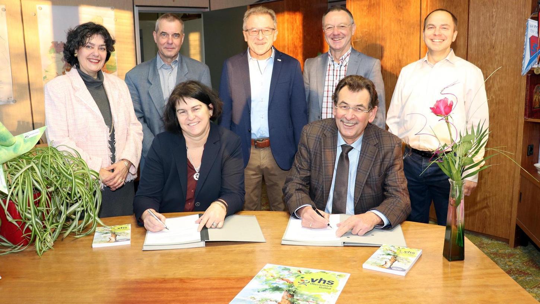 Den Kooperations-Vertrag ihrer Volkshochschulen unterzeichneten Birgit Huber und Johann Völkl. Mit auf den Weg gebracht haben ihn unter anderen Gabriele Olesch (links) und Gerhard Hable (stehend, 2. v. re.).