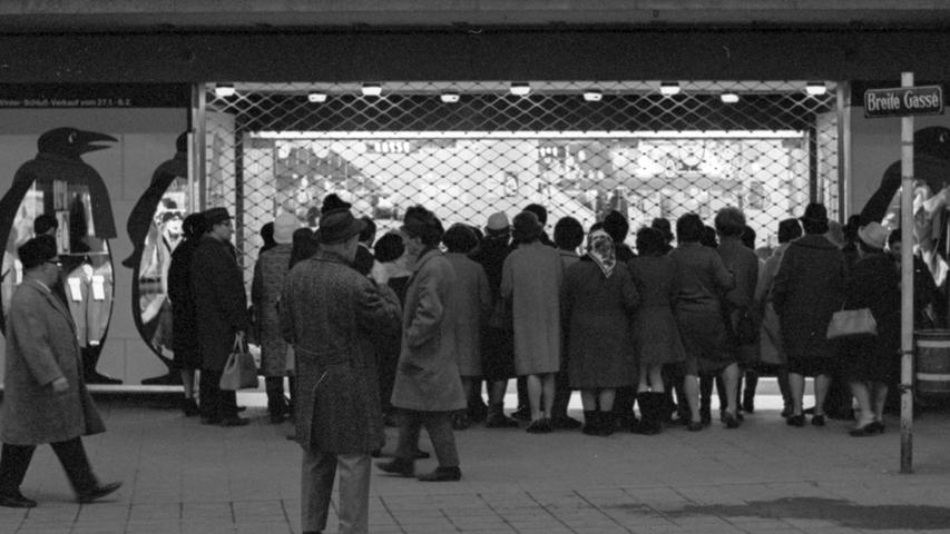 """So sah es heute vor 50 Jahren kurz vor 8 Uhr in der Innenstadt aus. Zahlreiche Frühaufsteher warteten darauf, daß das Gitter vor dem Eingang eines Kaufhauses hochging. Dann wurde es """"gestürmt"""". Hier geht es zum Kalenderblatt vom 28. Januar 1969: Mit sicherem Griff ...."""