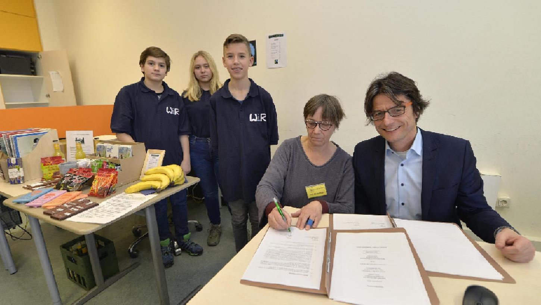 Gerald Wölfel (rechts), Schulleiter der Wirtschaftsschule im Röthelheimpark und Julie Mildenbacher (zweite von rechts) vom Dritte Welt Laden Erlangen unterschreiben den Kooperationsvertrag.