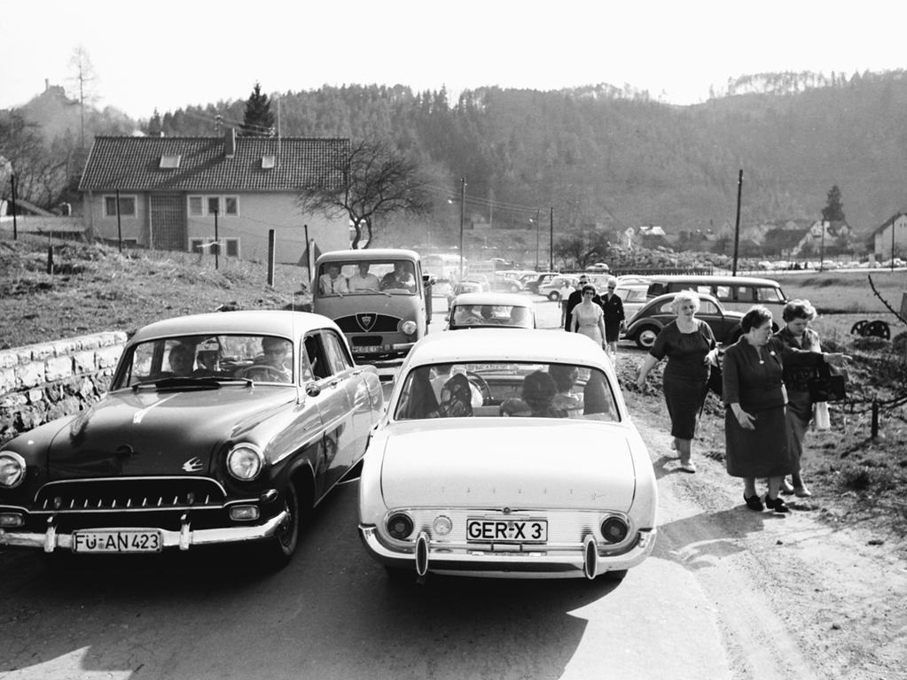 Motiv: Serie Osterausflug in die Fränkische Schweiz, hier: Wanderer neben Autoschlange. BU: Wanderer hatten es an den Osterfeiertagen nicht ganz einfach. Oft wurden sie - wie hier bei Behringersmühle - hart an den Straßenrand gedrängt und mit Staub bedeckt..Foto: Gerardi veröff. 24.04.1962..gespeichert April 2012, historisch, 1960er