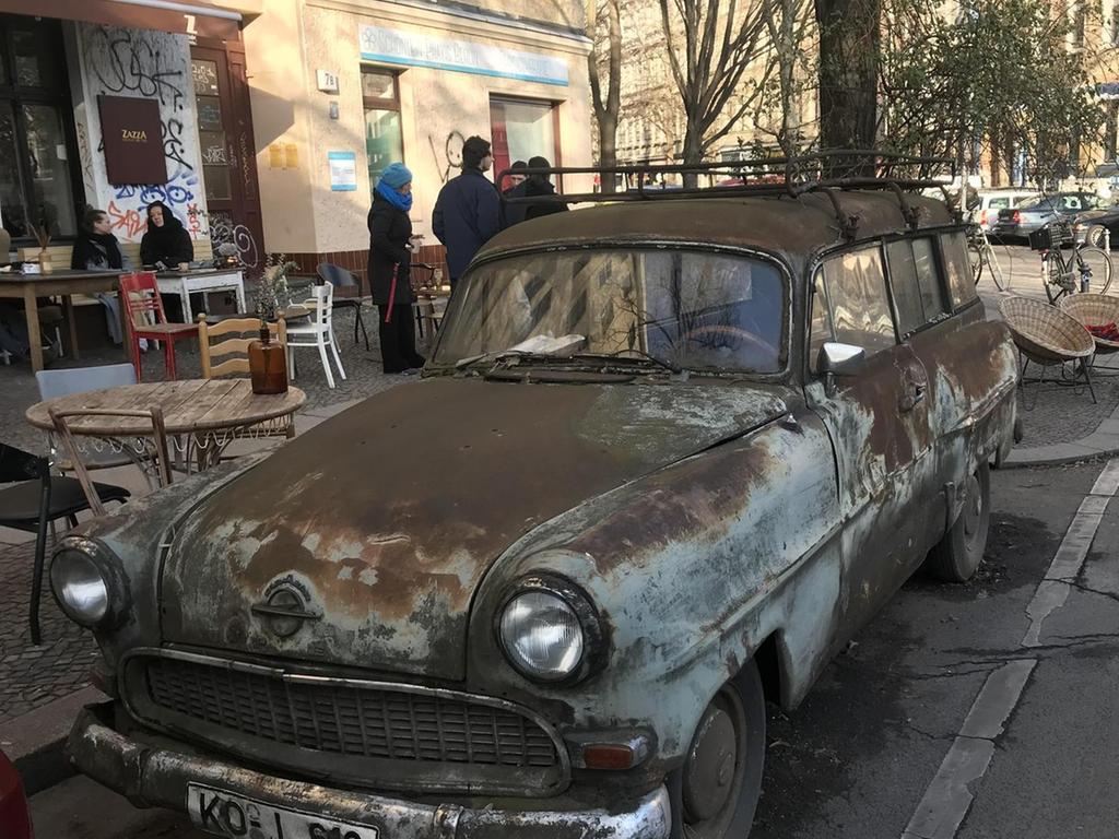 Ein stadtbekanntes und stets fahrbereites Wrack am Straßenrand in Kreuzberg.