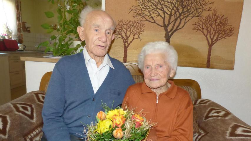 Barbara und Josef Sebald aus Hühnerloh sind seit 65 Jahren verheiratet und feierten am Valentinstag eiserne Hochzeit. Kennen und lieben gelernt hatten sie sich als Magd und Roßknecht bei der Arbeit. Der gebürtige Hühnerloher Josef Sebald war Roßknecht im früheren Metzgerei-Gasthaus Helldörfer in Gößweinstein, wo er auch die Landwirtschaft leitete. Seine Frau Barbara, eine geborene Deinlein aus Trägweis, war zur gleichen Zeit Magd. Vor 65 Jahren heirateten dann beide in der Klosterkirche am Bamberger Michelsberg. Es war eine Doppelhochzeit zusammen mit  Josef Sebalds Bruder und seiner Braut. Geheiratet wurde damals nicht, weil Valentinstag war, sondern ganz einfach, weil um die Zeit von Lichtmess die Dienstboten meist eine neue Stelle antraten und deshalb eine Woche frei hatten. Die standesamtliche Trauung dann durch den früheren Gößweinsteiner Bürgermeister Heinrich Pöhnlein an einem Sonntag in dessen Wohnzimmer, das gleichzeitig das Standesamtszimmer war. 1962 baute sich das junge Paar dann sein Haus in Hühnerloh, in dem beide heute noch leben, mit ihrem Sohn und Schwiegertochter Gabi, die die beiden liebevoll betreut. Auch ehrenamtlich waren beide aktiv. Josef Seblad war 35 Jahre lang Ortsführer von Hühnerloh und betreute bis zu seinem 85. Geburtstag die Hühnerloher Ortskapelle. Diese führt heute sein Sohn Eduard weiter. Seit mehr als 40 Jahren ist der heute 97-jährige Josef Sebald auch schon Mitglied des CSU-Ortsverbands Gößweinstein, der Soldatenkameradschaft und dem Verkehrs- und Heimatverein Gößweinstein. Seine acht Jahre jüngere Frau Barbara war viele Jahre im katholischen Frauenbund Gößweinstein aktiv.
