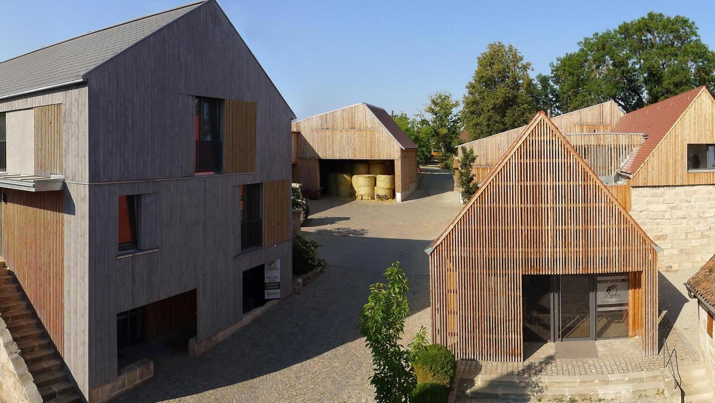 """Ein """"Blickfang mitten im Ort"""", befand die Jury: Sandsteinquader und Holz bestimmen die Handschrift des Architekten Peter Dürschinger. Von der restaurierten alten Schmiede (vorne re.) ausgehend, gestaltete Dürschinger Gebäude für Gebäude etwas moderner."""