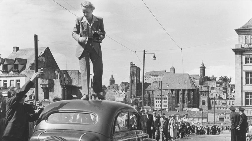 Um 1950 in der Nürnberger Königstraße: Gertrud Gerardi hat gerade einen Umzug fotografiert. Vom Dach des Opels aus bot sich ein guter Überblick und freie Sicht auf die Ruinen der Sebalder Altstadt. Ihr maßgeschneiderter Hosenanzug, der zum Markenzeichen der Fotografin wurde, war bei ihren Klettertouren unverzichtbar, jedoch nicht überall gerne gesehen in einer Zeit, als Frauen noch Röcke zu tragen hatten!