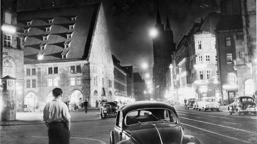 """WOW! 1953 in der nächtlichen Königstraße leuchtet hinter dem einsamen Betrachter und dem VW-Käfer die aus Ruinen wiedererstandene Mauthalle hell auf in der zur Ruhe gekommenen Stadt. Gertrud Gerardi ist ehemaligen Kollegen als energisch, optimistisch und zukunftsgewandt in Erinnerung. Auch deshalb sei sie zur """"Kronzeugin des Wiederaufbaus"""" geworden, schwärmte Wolfgang Buhl in seinem Nachruf 2002."""