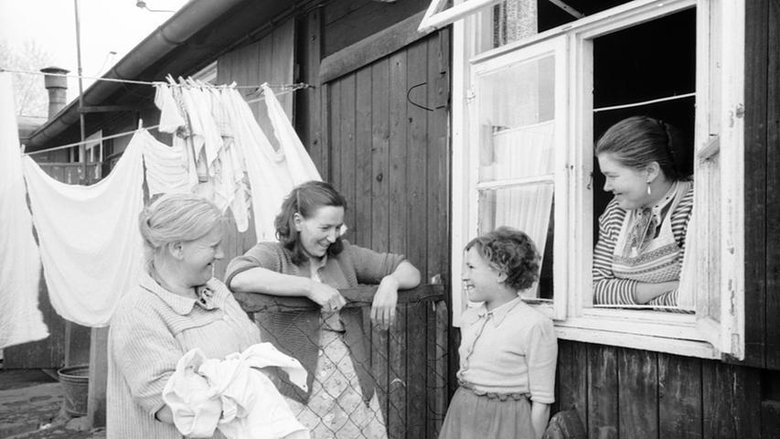 """Gestern noch mondäne Mode, heute Wäsche im Witschellager! - In der Barackenwohnanlage in der Nürnberg Witschelstraße, die Gertrud Gerardi 1957 mit ihrer Kamera festhielt, """"hockt das Elend"""", schrieben damals die NN. Während die Bildjournalistin eine Aufnahme nach der anderen machte, ließen sich die Frauen überhaupt nicht stören in ihrem Alltag. Gerardi gelang es immer wieder, den Leuten die Scheu vor der damals vielfach noch ungewohnten Kamera zu nehmen und sich ungezwungen und natürlich zu geben."""