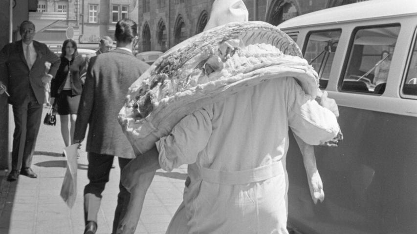 """Unterwegssein - Sehen - Erkennen - Draufhalten.  Auch das macht den optischen Menschen und die gute Fotografin aus! Dieses Gerardi-Bild zeigt einen Metzger, der mal eben mit einer Schweinehäfte aus seinem Geschäft mitten in der Nürnberger Innenstadt tritt und das """"Suggerla"""" zum Auto der Kundschaft trägt, die demnächst daraus daheim ihre Hausmacherwurst zubereiten würde. Die letzten Reste der Hausschlachter-Tradition sollten bald schon zugunsten von Tiefkühl-Koteletts verschwunden sein."""
