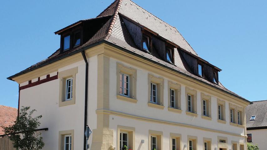 """Gegenüber der ehemaligen Poststation von Langenfeld, die bis zum Niedergang des Posthalterwesens nach dem Bau der Bahnstrecke Würzburg-Nürnberg für den Ort einen wichtigen Wirtschaftsfaktor darstellte, steht das ehemalige """"Gasthaus zum Hirschen"""". Der zweigeschossige Walmdachbau stammt vermutlich aus der Mitte des 18. Jahrhunderts. Die Straßenfassade aus Sandsteinquadermauerwerk ist mit einem Ecklisenen, Gurtgesims, und geohrten Fensterrahmungen im Obergeschoss ausgezeichnet. Zurückgenommener gestaltet sind die der Straße abgewandten Seiten. Hofseitig ist das auf einem L-förmigen Grundriss errichtete Gebäude fachwerksichtig."""