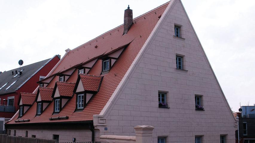 Eine fast unglaubliche Verwandlung vom ruinösen Schandfleck zum attraktiven Hingucker hat ein ehemaliges Wohnstallhaus in Nürnberg-Schniegling durchgemacht.  Der eingeschossige Sandsteinquaderbau mit steilem, dreigeschossigem Satteldach stammt wohl aus dem frühen 18. Jahrhundert und wurde bis 1838 komplett versteinert. Er weist die für die Nürnberger Umgegend typischen Volutengiebel und Aufsatzvasen an den Giebeln und – jetzt wieder – eine charakteristische Fassadenbemalung auf. Der bauzeitliche Grundriss ist teilweise noch gut ablesbar.  Die Geschichte seines dramatischen Verfalls ist leider kein Einzelfall: Der Umgriff des ungenutzten Denkmals wurde nach und nach bebaut, bis letztlich nur noch der historische Bau ohne nennenswerten Grund und Boden, mehr oder weniger als Störfaktor inmitten moderner Wohnhäuser, übrig blieb. Fast 20 Jahre stand das Bauernhaus leer. Zuletzt war es extrem marode und akut einsturzgefährdet. Seine beiden mächtigen Steingiebel wurden nur noch mittels quer durchs Haus gespannter Ketten zusammen gehalten. Durch den tieferliegenden benachbarten Neubau war der Ostgiebel außerdem abgesackt und hatte sich bedrohlich geneigt.