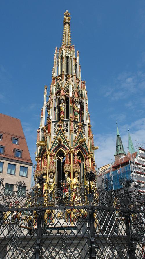 """Der """"Schöne Brunnen"""" auf dem Hauptmarkt gehört zu den wichtigen touristischen Attraktionen in der Nürnberger Altstadt. Die stark durchbrochene mehrstufige Steinpyramide in gotischen Formen mit ihrem religiösen und weltlichen Figurenprogramm mit fast 40 Skupturen wurde ursprünglich 1389 bis 1396 als öffentlicher Brunnen in Sandstein errichtet. Nach mehreren Jahrhunderten, in denen das Material immer mehr verwitterte, schuf man von 1897 bis 1902 eine Kopie aus dem härteren Muschelkalkgestein."""