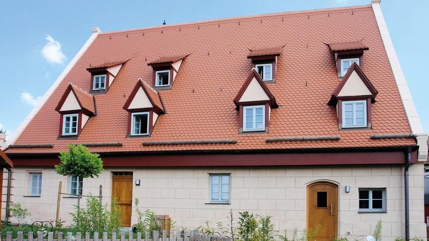 """Erst nachdem auch noch die Sparren an den – teilweise neu errichteten - Giebelwänden verankert waren, konnten die stabilisierenden Ketten entfernt und ein denkmalgerechter Innenausbau in Angriff genommen werden. Entstanden sind vier Wohneinheiten, die moderne und historische Elemente miteinander verbinden.  Die auffälligste Veränderung hat die Fassade erfahren. Im Zuge der umfangreichen Voruntersuchungen war eine regionaltypische Quadermalerei gefunden worden, mit der das Haus schon früh gefasst worden war. Diesem besonderen Befund im sogenannten """"Nürnberger Rot"""" mit dunkleren Fugenstrichen folgt die aktuelle Neufassung des gesamten Gebäudes.  Eine schier unendliche Liste an tiefgreifenden Maßnahmen und findigen Ingenieurslösungen hat aus einem schon aufgegebenen Haus ein Vorzeigebeispiel früheren ländlichen Bauens im Nürnberger Umland werden lassen. Dem Bauherrn ist zu danken für seinen Mut, seine Tatkraft und seine Ausdauer."""