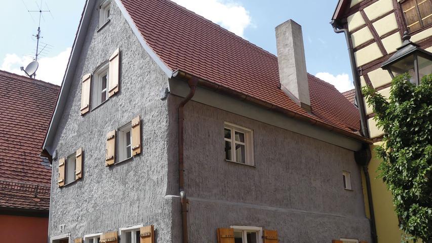 Versteckt in einer Gasse liegt das schmale Kleinhaus abseits der Hauptstraße. Der zweigeschossige Satteldachbau mit Fachwerkobergeschoss stammt aus dem 17. oder 18. Jahrhundert. Für großes Erstaunen sorgte der hohe Grad an noch vorhandener historischer Ausstattung. Viel jünger, aber nicht weniger außergewöhnlich, ist der auffällige Fassadenputz: der sogenannte Besenstrichputz war im 19. und beginnenden 20. Jahrhundert eine findige Weise, kostspielige Natursteinoberflächen zu imitieren. Leider zeichneten das Gebäude zuletzt große Feuchtigkeitsschäden. Stark beeinträchtigt zeigten sich Außenputz und Fachwerk. 2013 erwarb der neue Eigentümer das besondere Kleinhaus und renovierte es über drei Jahre hinweg für eine neue Nutzung als Ferienhaus.  Man entschied, dem mehrere Jahrhunderte alten Haus sein junges Gesicht zu lassen: Der Besenstrichputz wurde nicht abgenommen, sondern erhalten und wo nötig ergänzt. Der reiche Bestand an alten Stulpfenstern wurde saniert. Nur wenige neue Holzfenster komplettieren zusammen mit den neuen Fensterläden die heutige Ansicht. Nicht erhalten werden konnten die alten Dachziegel. Nach Ausbesserungsarbeiten am Dachstuhl deckte man das Satteldach mit roten Biberschwanzziegeln neu ein. Im Inneren setze man geschädigte Balken und Gefache instand, Nur an sehr lädierten Stellen ergänzte oder erneuerte man die Hölzer. Neben dem Einbau von Lehmbauplatten restaurierte man außerdem die alten Bohlen-Balken-Decken.